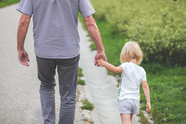 grandfather and granddaughter walking holding hands