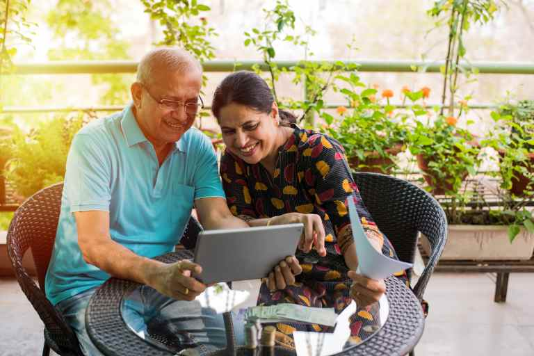 indian couple smiling looking at computer