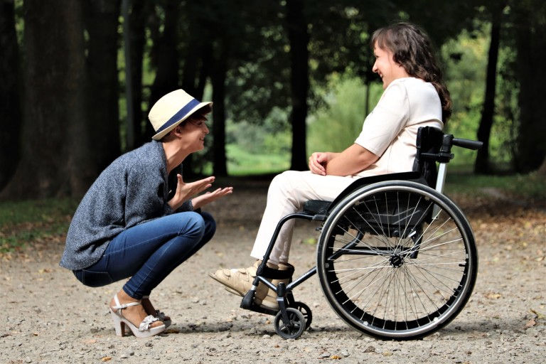 lady kneeling next to woman in wheelchair