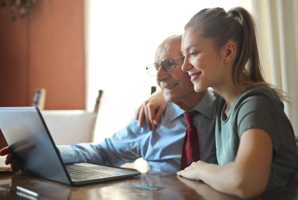 smiling woman helping senior man use computer